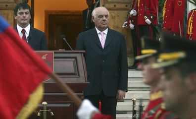 Former Albanian President Alfred Moisiu looks at honour guards with new President Bamir Topi (L) during a ceremony in the Palace of Brigades in Tirana