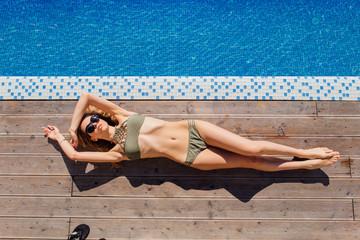 Beautiful slim sexy woman in a bikini relaxing near the pool