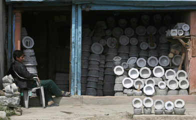A boy waits for customers as he sells kitchen items made of stones at his shop in Panthachowk