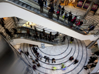 People walk through a shopping centre in Canary Wharf