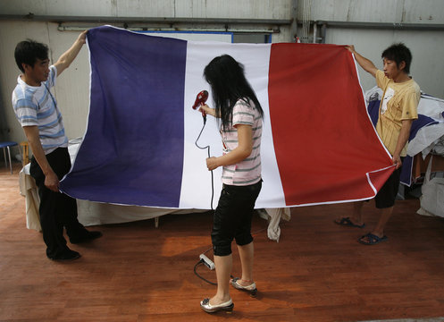 Two male workers hold a French flag as a woman uses a hair dryer to remove creases at the Beijing Jingong Red Flag factory