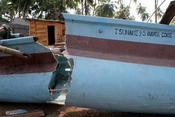Broken fishing boat lays near the wrecked coach of a tsunami-hit train in Peraliya, Sri Lanka.