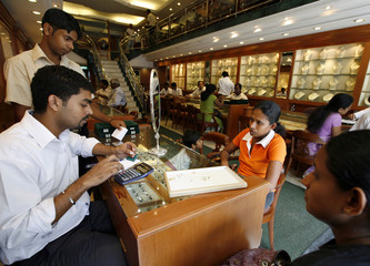 Salesmen attend to customers as others browse through gold jewellery inside shop in Colombo