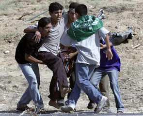 PALESTINIAN CARRY WOUNDED YOUTH AFTER BEING SHOT BY ISRAELI SOLDIERS INGAZA.