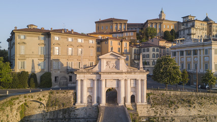 Bergamo - Old city. One of the beautiful city in Italy. Aerial shot of the old gate named Porta San Giacomo during the sunrise and a wonderful blu day