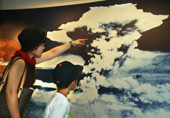 MOTHER AND SON LOOK AT A PICTURE OF MUSHROOM CLOUD A-BOMB BLAST INHIROSHIMA.