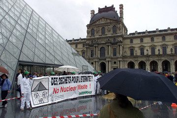 A tourist takes cover under an umbrella as she stops to look at Greenpeace demonstrators who stage a..