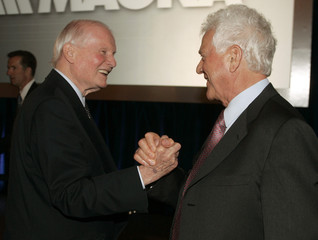Magna International Inc. Chairman Stronach shakes hands with former Ontario Premier Davis at end of Magna's annual general meeting of shareholders