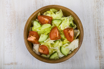 Salad in wooden bowl on a table close-up.
