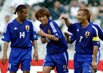 Japan's Shunsuke Nakamura (C) celebrates his goal with Alessandro Santos (L) and captain Hidetoshi N..