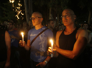 Israelis take part in a candlelight vigil for the victims of a shooting incident at a basement club in central Tel Aviv