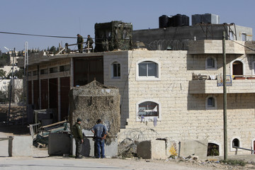 Israeli border police speak to a Palestinian next to a disputed building occupied by Jewish settlers in the West Bank city of Hebron