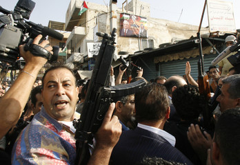 Palestinian armed men react as news journalists try to enter Burj al-Barajneh refugee camp in a Beirut suburb