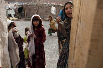 An Afghan woman and her daughters talk to a photographer during a patrol by U.S army soldiers from Task Force Denali 92 MP at Ghurki Kholah village