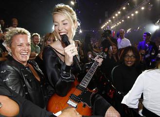 Sharon Stone sits on the lap of bidder Charlene DiLorenzo at the 2006 Macy's Passport gala in Santa Monica