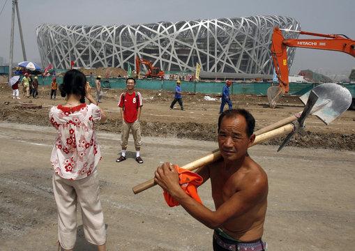 A man carries tools on his shoulder as he walks past tourists taking pictures of the Olympic Stadium in Beijing