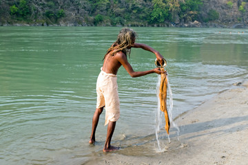 INDIA, LAXMAN JHULA - APRIL 17, 2017: Sadhu washing clothes at the river Ganges in Laxman Jhula on 17th of april 2017