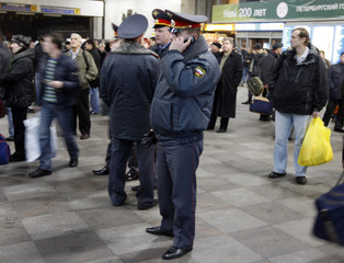 Police officer speaks on the phone while passengers wait as train services were suspended at Moskovsky train station in St. Petersburg