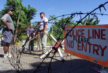 Police and barbed wire block the entrance to Fiji's parliament in Suva May 20. George Speight and ar..
