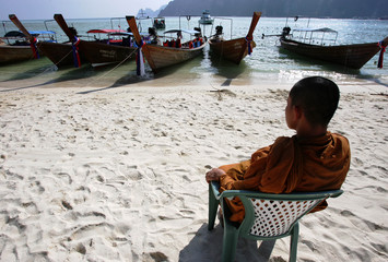Buddhist monk recites prayers for boats during ceremony to commemorate first anniversary of tsunami on Thailand's Phi Phi island