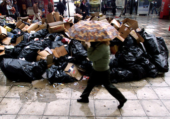 AN ATHENIAN WALKS PAST A PILE OF GARBAGE AT GREECE'S CENTRAL SYNTAGMASQUARE.