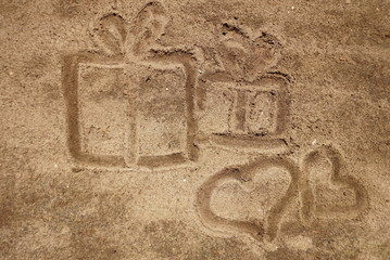 two hearts drawn in the sand with gifts