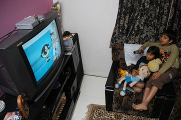 Indian boy watches cartoon with his sister in Bangalore
