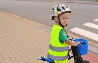 Little boy riding bike in front of zebra crossing. He wears helmet and reflective vest with stripes.