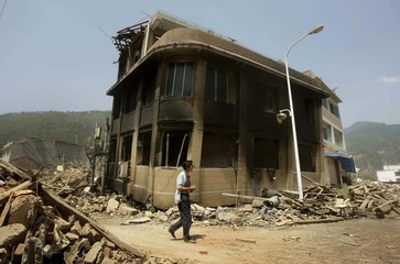 Earthquake survivor walks past a damaged building in Nanba town of earthquake-hit Pingwu county