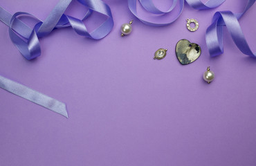Background with silver, crystal, pearl and charms and heart mother of pearl pendant isolated on purple withsatin ribbon as frame at top - Mothers day