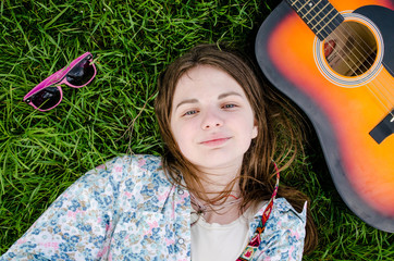 Beautiful free teen relaxing on the grass summer