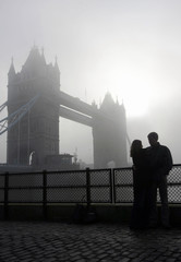 A couple are silhouetted in front of the Tower Bridge during foggy conditions in London