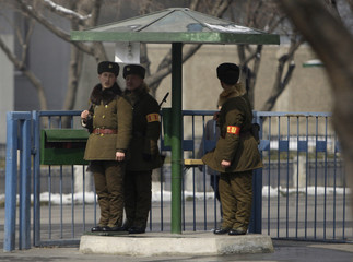 North Korean soldiers stand under a shelter on a street in Pyongyang