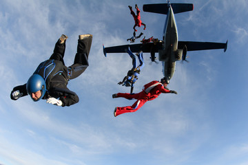 Skydivers are jumping out of a plane