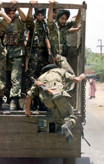 AN INDIAN SOLDIER JUMPS ONTO TRUCK IN AHMEDABAD.