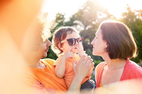 Family with child walks and plays in city park. A young father, mother and a small son dressed in orange t-shirt. The child funny dresses up sunglasses and plays with them. Child in the hands of his