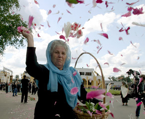 WOMAN THROWS FLOWERS ON ROAD AS ICON OF VIRGIN MARY IS CARRIED THROUGH TIKHVIN IN RUSSIA.