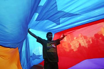 Supporter of Venezuelan President Hugo Chavez stands under a flag in Caracas