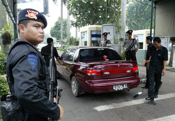 An armed Indonesian policeman stands guard at the entrance of Jakarta's Hilton hotel.