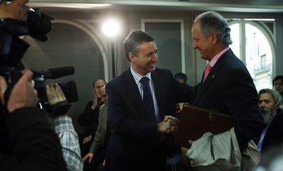 Former president of the regional Basque parliament Atutxa is greeted by the president of the PNV Urkullu before a news conference in Bilbao
