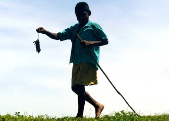 A young Miskito carries a dead rat in northern Nicaragua