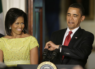 First lady Michelle Obama smiles as President Barack Obama looks at his watch at the celebration of Cinco de Mayo in Washington