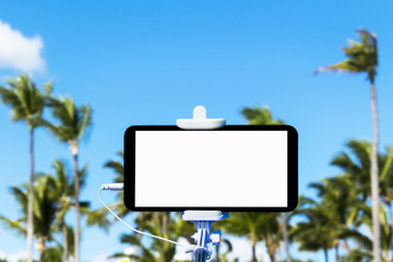Selfie monopod stick with mobile phone, tropical background, empty space for text, white screen