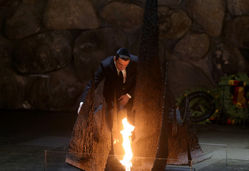 Sorin Grindeanu, Romania's Prime Minister, rekindles the eternal flame, commemorating the six million Jews killed by the Nazis in the Holocaust, during a ceremony in the Hall of Remembrance at Yad Vashem Holocaust memorial in Jerusalem