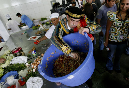 Spanish inmate Carlos Andujar, wearing traditional clothing, makes a salad during a cooking competition at Sarita Colonia prison in Callao