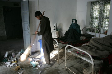 A man sweeps a hospital ward as an injured woman sits on a bed in Karnah
