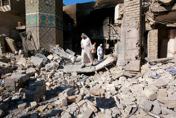 A man walks through rubble after a Shi'ite mosque was destroyed by an explosion in Baghdad.