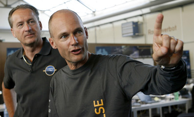 Piccard, pilot and president of Solar Impulse stands beside Borschberg, CEO and pilot of the company after a 25-hour flight simulation in a life-size model of the cockpit of the HB-SIA prototype airplane at the airport in Duebendorf near Zurich