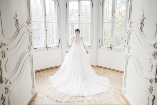 The charming bride stands near windows