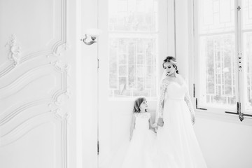 The beautiful bride with daughter standing near windows